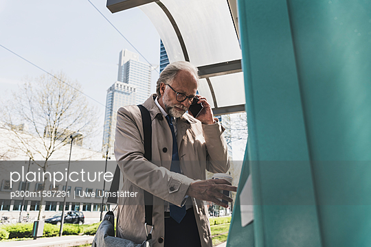 Mature businessman with cell phone and takeaway coffee in the city at tram station - p300m1587291 von Uwe Umstätter
