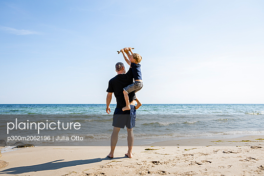 Father and son playing at the beach - p300m2062196 von Julia Otto