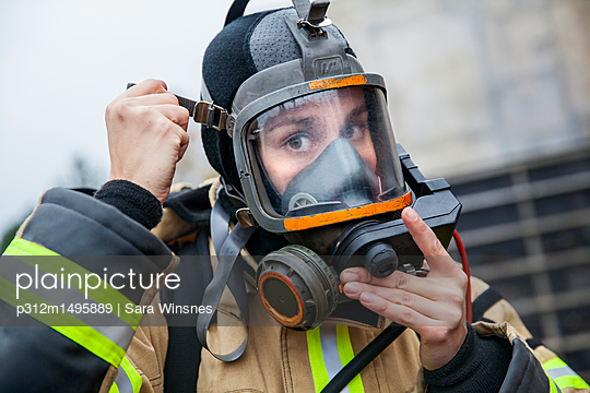 Firefighter woman putting mask on