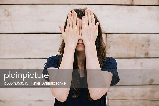 Junge Frau mit Händen vor Gesicht - p586m953519 von Kniel Synnatzschke