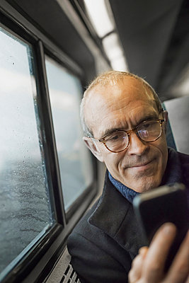 A mature man sitting by a window in a train carriage, using his mobile phone, keeping in touch on the move. - p1100m876838f by Tim Pannell
