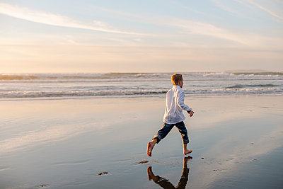 Back view of boy running on water by the sea - p1166m2073871 by Cavan Images