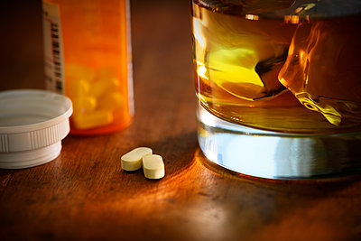 Glass of whiskey and oxycodone - p1427m2038494 by Tetra Images