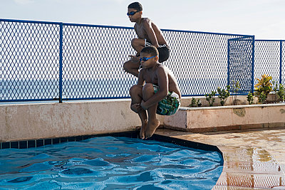 Two boys doing a cannonball dive into swimming pool - p300m1140652 by Mauro Grigollo