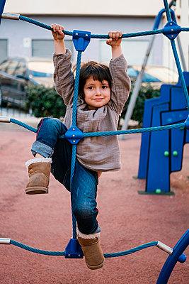 Girl on climbing net in playground - p300m2198083 by Ezequiel Giménez
