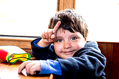 Cute boy smiling and pointing finger - p429m2127758 by Bonfanti Diego