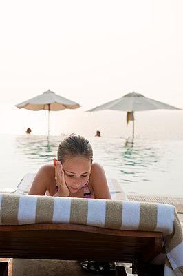 Teenage girl sunbathing on lounge chair - p575m1074521f by Fredrik Schlyter