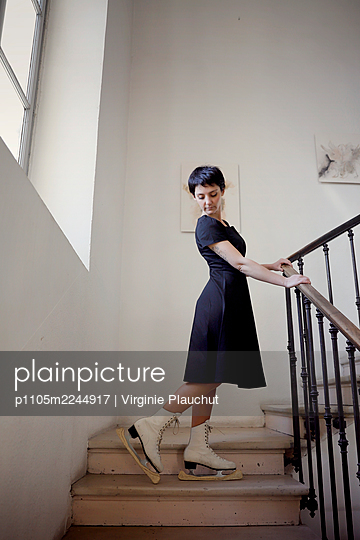 Woman in black dress and skates in the stairwell - p1105m2244917 by Virginie Plauchut