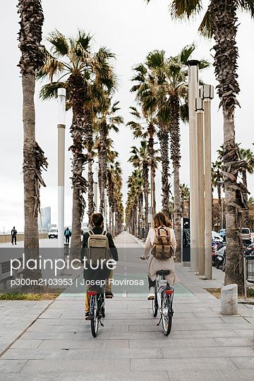 Rear view of couple riding e-bikes on a promenade - p300m2103953 by Josep Rovirosa