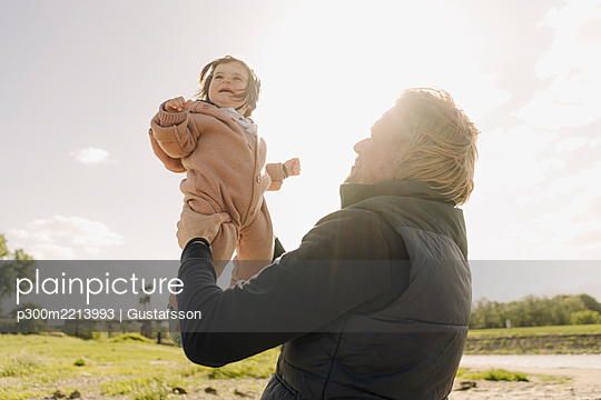Father picking up baby daughter while standing near river bank on sunny day - p300m2213993 by Gustafsson