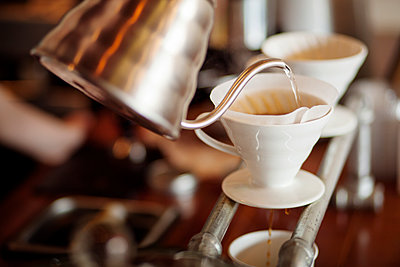 Water being poured from kettle into coffee filter at cafe - p1166m1144825 by Cavan Images