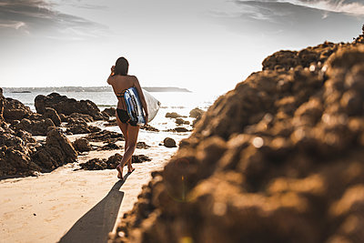France, Brittany, young woman carrying surfboard on a rocky beach at the sea - p300m2059670 by Uwe Umstätter