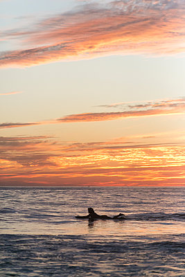 Woman in silhouette with cowboy hat on surfboard  - p919m2108336 by Beowulf Sheehan