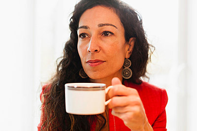 Woman drinking cup of coffee - p924m757087f by Image Source
