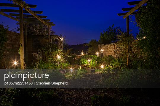 Ländlicher Garten mit Kerzen beleuchtet - p1057m2291450 von Stephen Shepherd