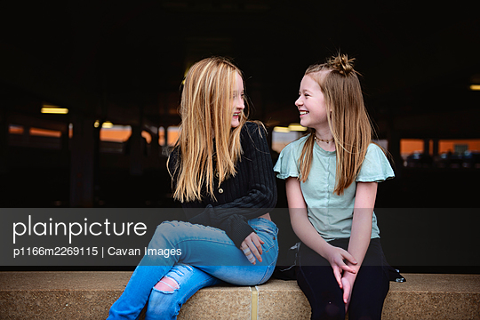 Two happy tween girls sitting on a brick wall together. - p1166m2269115 by Cavan Images