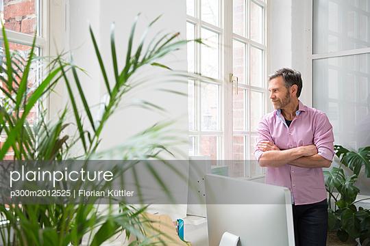 Man looking out of window in office - p300m2012525 von Florian Küttler