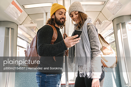 Young couple using smartphone on a subway - p300m2154537 by Hernandez and Sorokina