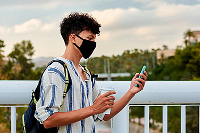 Young afro-haired man with mask is using his mobile on the street - p1166m2201825 by Cavan Images