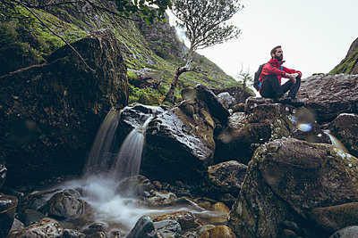 Thoughtful male hiker sitting on rock near the water fall - p1315m1564966 by Wavebreak