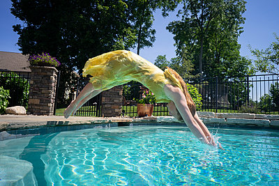 Woman in yellow dress jumping in the pool - p1554m2272600 by Tina Gutierrez