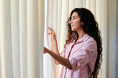 Woman looking out of window, portrait - p1640m2254683 by Holly & John