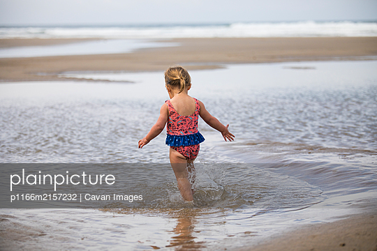 Rear view of young girl running through tidal pool at the beach. - p1166m2157232 by Cavan Images