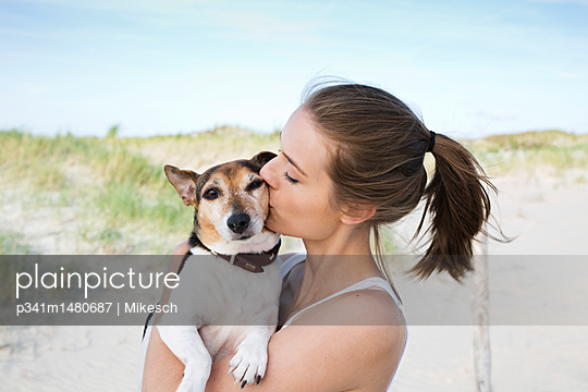 Young woman on beach playing with dog - p341m1480687 by Mikesch