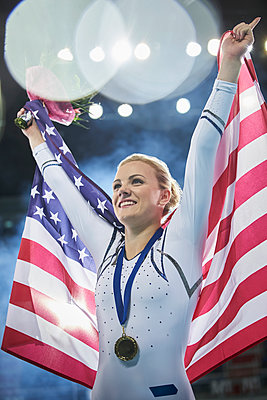 Smiling female gymnast celebrating victory holding American flag - p1023m1217726 by Chris Ryan
