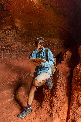 Young man sitting in a cave, looking through binoculars, holding map - p300m2059796 by VITTA GALLERY