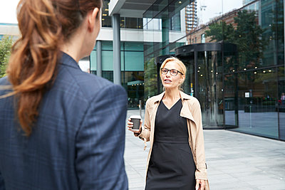 Colleague talking with businesswoman standing st distance in city - p300m2227075 by Pete Muller