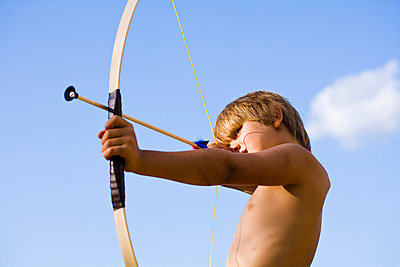 Shirtless boy aiming bow and arrow - p312m695529 by Plattform photography