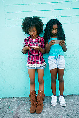 Girls leaning on wall texting on cell phones - p555m1472923 by Peathegee Inc