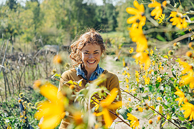 Young woman stands next to sunflower field - p586m1214253 by Kniel Synnatzschke