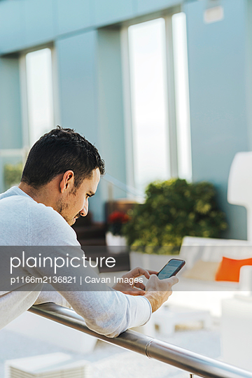 Young man leaning on railing while using mobile phone - p1166m2136821 by Cavan Images