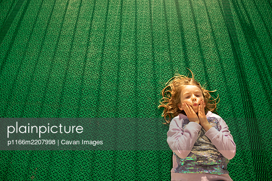 Girl Laying on Green Floor With Funny Expression in Helsinki, Finland - p1166m2207998 by Cavan Images