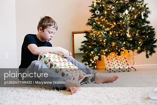 Junge mit Weihnachtsgeschenken - p1262m1198432 von Maryanne Gobble