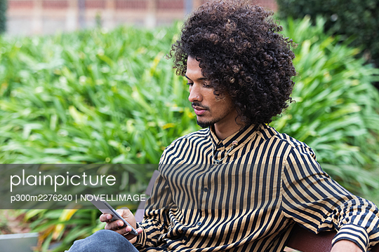 Young man using mobile phone in public park - p300m2276240 by NOVELLIMAGE