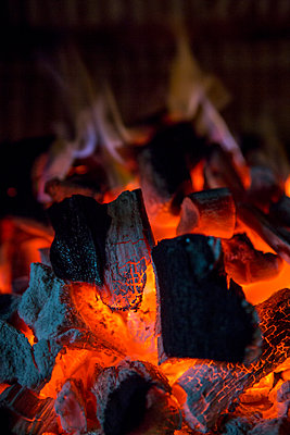 Looking on to charcoal briquettes and wood glowing with ornage flames as the coal reaches the temperature for cooking on an outdoor BBQ. - p1057m2020724 by Stephen Shepherd