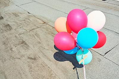 Bunte Ballons auf einem Flachdach - p1076m1582553 von TOBSN