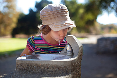 Girl drinking water from faucet - p1166m1099522f by Cavan Images