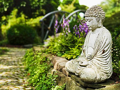 Stone statue of seated Buddha on rough, low stone wall lends meditative atmosphere to ornamental garden with cobbled path leading to small bridge - p1183m996936 by Sweetdelights