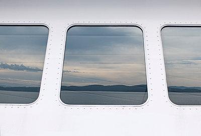 Landschaft spiegelt sich in Fenstern einer Fähre - p240m1196411 von Valerie Wagner