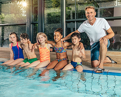 Portrait of smiling children with instructor sitting on poolside in indoor swimming pool - p300m1535511 by Mareen Fischinger