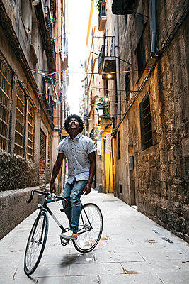 Spain, Barcelona, man standing with racing cycle in an alley looking up - p300m2023841 von Josep Rovirosa