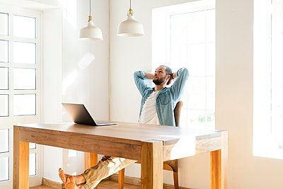 Serious young man with laptop in home office having a break - p300m2180604 by Steve Brookland