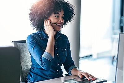 Smiling female customer service representative talking through headphones at desk in office - p300m2275657 by Josep Suria