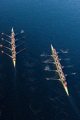 Elevated view of two rowing eights in water - p300m982144f by zerocreatives