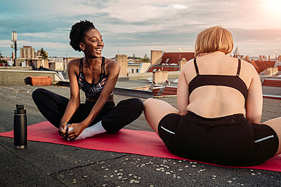 Smiling female friends exercising on rooftop - p426m2233487 by Maskot