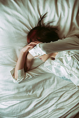 Young woman laying down in bed hiding her face  - p794m1476423 by Mohamad Itani